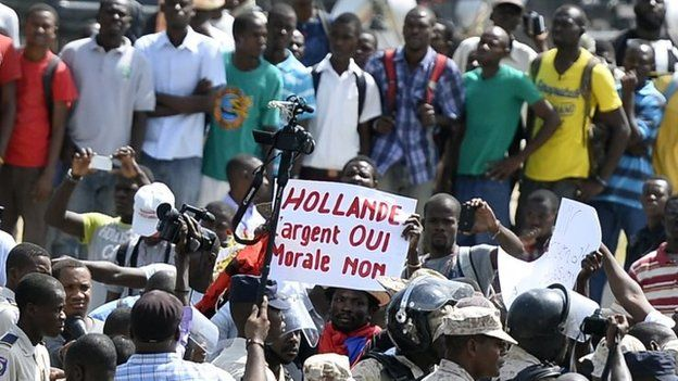 """2015, manifestations en réaction à la venue de François Hollande en Haïti. Ce dernier a affirmé que la France a une """"dette morale"""" envers Haïti."""