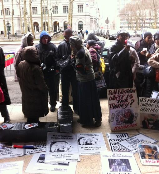 """2015, activistes haïtiens manifestant devant le quartier général d'Hillary Clinton à Brooklyn. Entre autres, on peut lire sur une des pancartes """"Bill Clinton, où est passé l'argent ?""""."""
